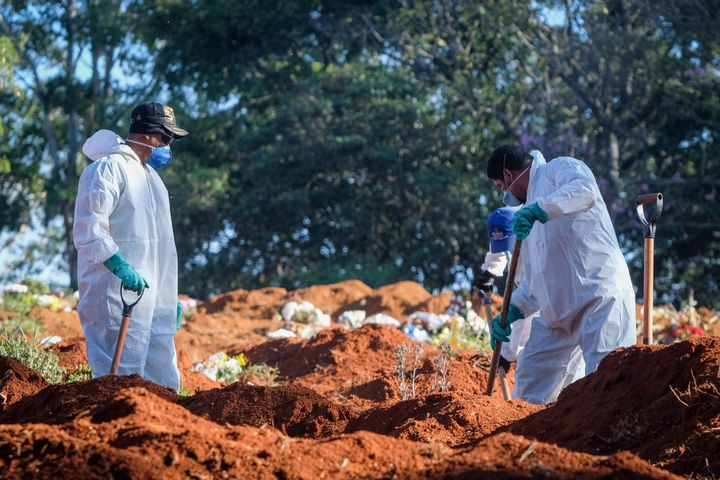 Cemetery workers in protective suits shovel earth at the Vila Formosa cemetery in the Brazilian city of Sao Paulo amid the co