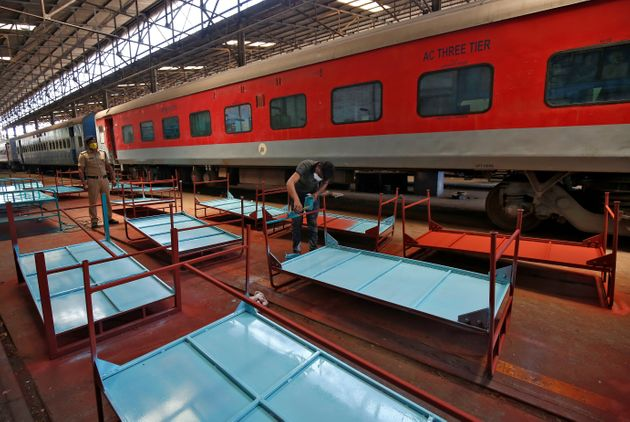 A worker paints beds to be used at a railway hospital in Chennai, India, to accommodate coronavirus patients,...