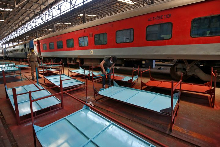 A worker paints beds to be used at a railway hospital in Chennai, India, to accommodate coronavirus patients, March 30.