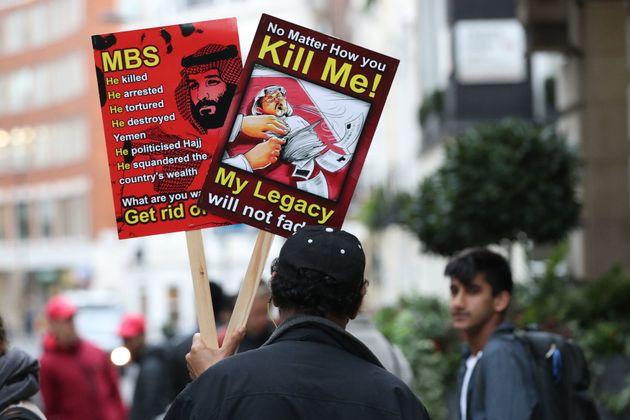 A man holds posters denouncing Saudi Crown Prince Mohammed bin Salman and hailing killed journalist Jamal...