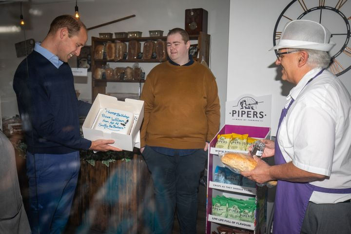 William is presented with a birthday cake by shop owner Paul Brandon (right).
