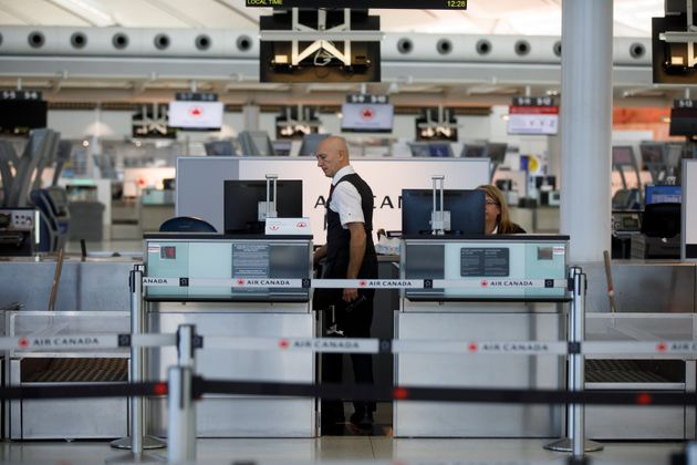 An Air Canada employee at a quiet check-in counter at Toronto Pearson International Airport, on April...