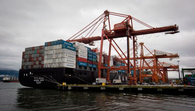 A container ship is unloaded at port in Vancouver on Dec. 23,