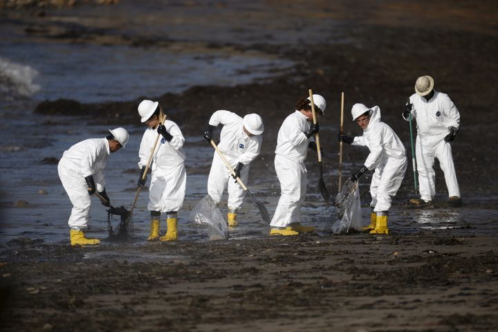 Workers clean an oil spill on a California beach. There's plenty more work where that came from.
