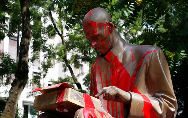 Red paint is seen on a statue of late Italian journalist Indro Montanelli, inside a park in Milan, northern...