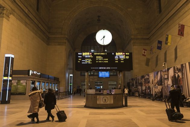 People make their way through Union Station in Toronto as the departure display for Via Rail show all...