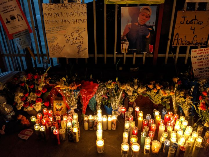 Candles and flowers are set next to an image of Andres Guardado.