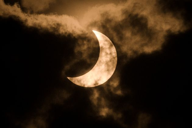 The partial solar eclipse is captured using infra red filter in the cloudy sky in Nairobi, Kenya on June...