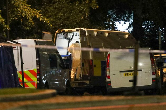 Forensic officers work at Forbury Gardens park where a stabbing attack took place Saturday, in