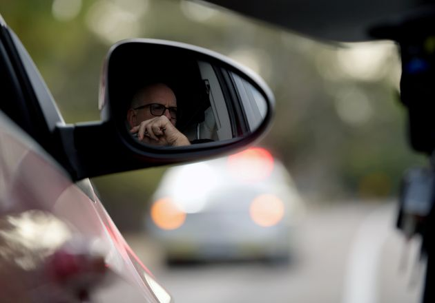 A motorist waits in a car as he crosses into South Australia from Victoria during the coronavirus disease...