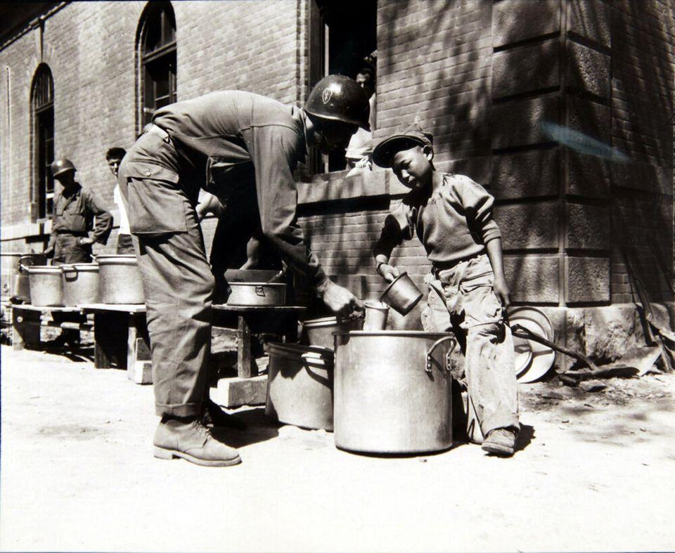 1950년 9월 23일 미군 부대에서 한 소년이 미군에게 커피를 퍼주고 있는 모습. 전쟁으로 부모를 잃은 고아 중 일부는 '부대 마스코트(unit mascot)'라고 하여, 미군 부대에서...