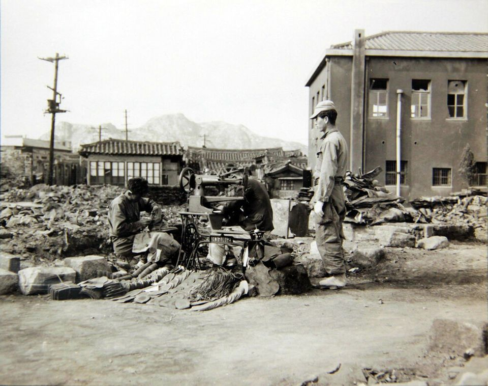 1950년 10월 28일 서울 수복 후, 한 수선공이 자기 가게가 있던 자리에서 다시 영업을 하며 전투화를 수선하는 모습. 2018년 6월 22일