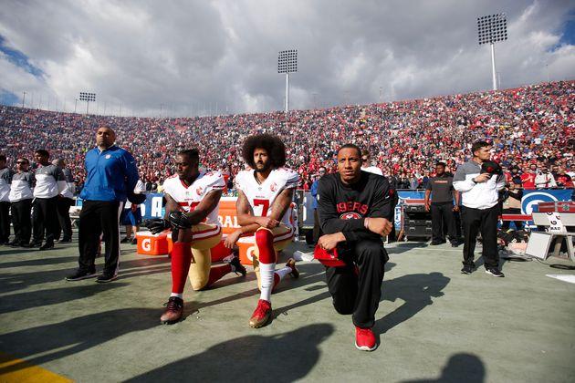 2016年12月、NFLの試合で国歌斉唱中に抗議のため膝をつくコリン・キャパニック氏(中央)