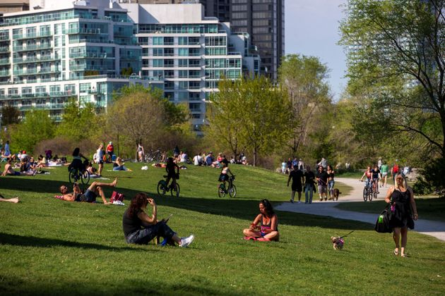 People maintain social distance as they sit at Humber Bay Shores park in