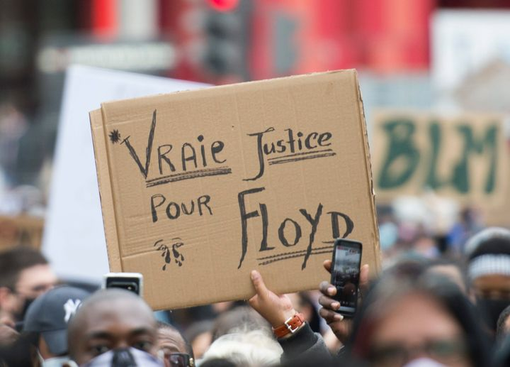 Des gens brandissent des pancartes lors d'une manifestation à Montréal réclamant justice pour la mort de George Floyd et de toutes les victimes de la brutalité policière le 31 mai dernier.