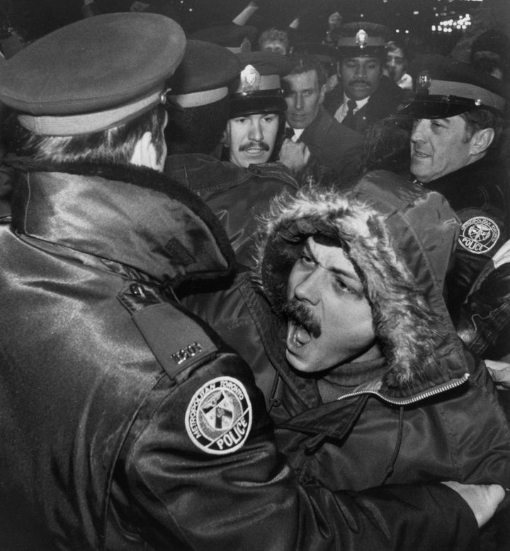A man is restrained by Toronto police outside the Ontario Legislature after about 1,000 gay rights demonstrators marched through the downtown area protesting the February 5, 1981 arrest of nearly 300 men in four city steam baths.