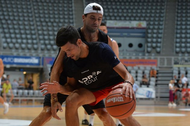 In this photo taken on Thursday June 18, 2020, Bulgarian tennis player Grigor Dimitrov, rear, plays basketball...