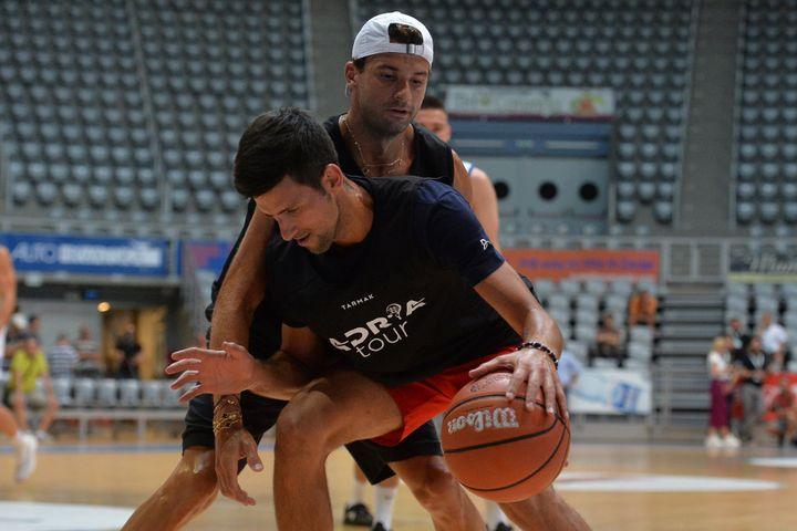 In this photo taken on Thursday June 18, 2020, Bulgarian tennis player Grigor Dimitrov, rear, plays basketball with Serbia's Novak Djokovic in Zadar, Croatia.