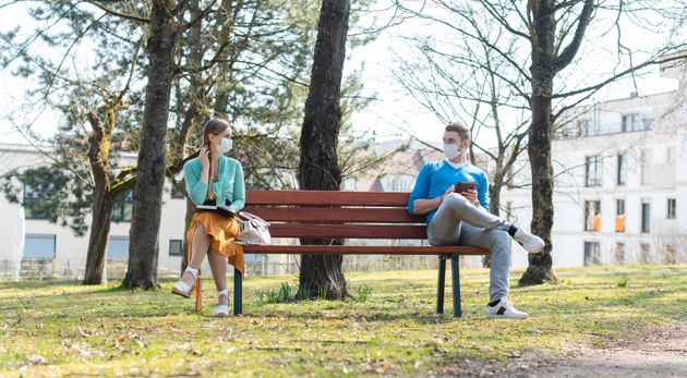 A woman and a man sit on a bench while distancing at a park in this stock photo. Canadian public health...