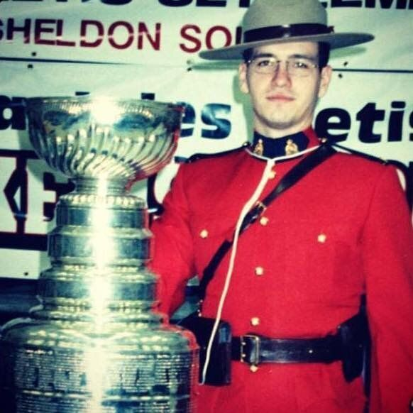 The writer poses next to the Stanley Cup in his RCMP red serge.