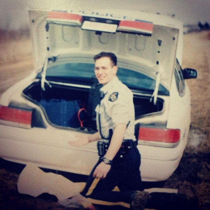 The writer smiles behind a stuck police car.