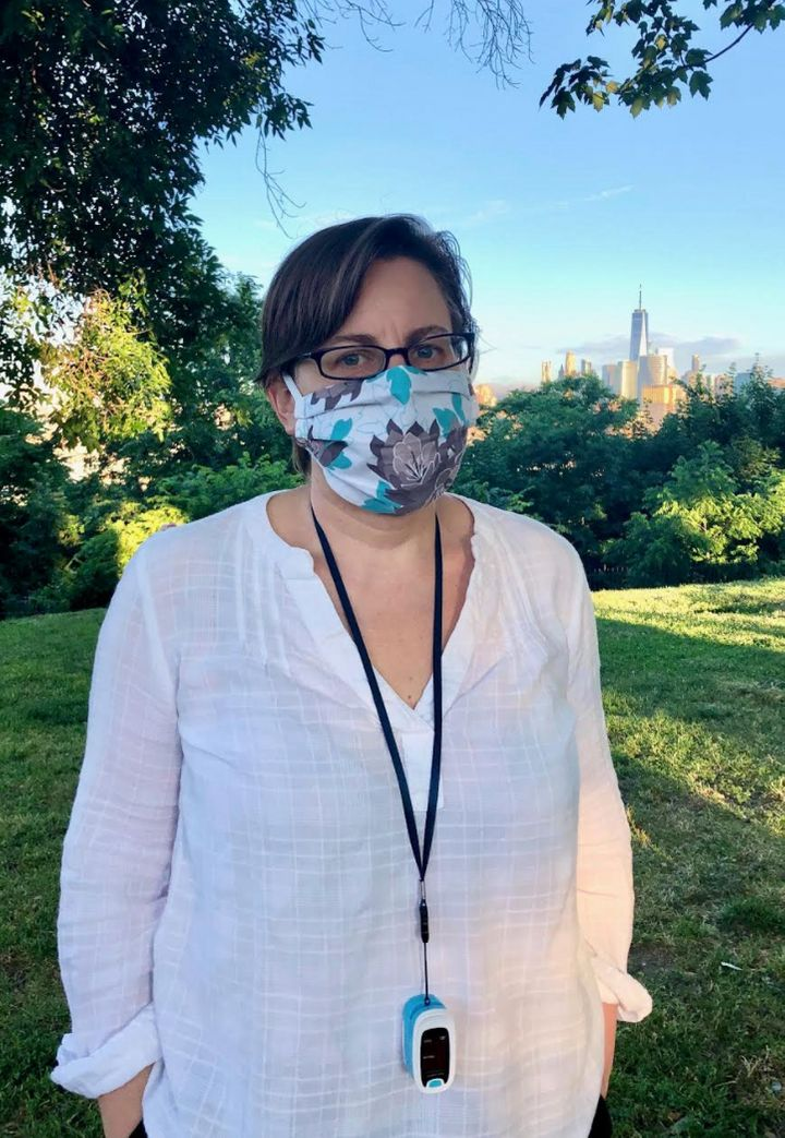 The author, masked and with her oximeter around her neck, on a walk in her Jersey City neighborhood with the Freedom Tower in the background in June 2020.