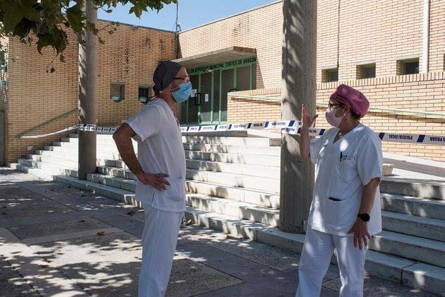 Dos sanitarios conversan a la salida del hospital de Fraga (Huesca), donde están aislados varios pacientes...