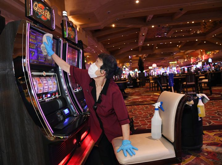An employee sanitizes slot machines at Excalibur Hotel & Casino after the property opened for the first time since mid-Ma