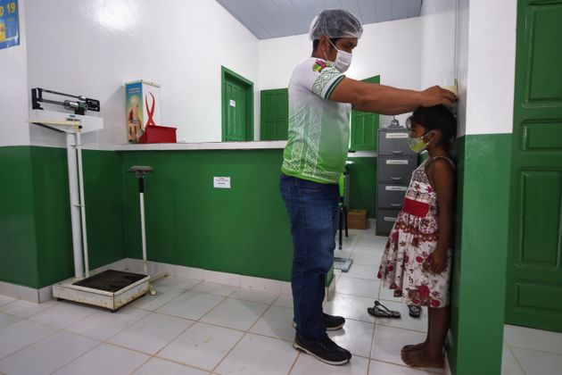 An indigenous girl of the Ticuna ethnic group receives medical assistance at a health post in the Umariacu...