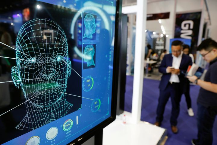 Visitors check their phones behind the screen advertising facial recognition software during Global Mobile Internet Conferenc
