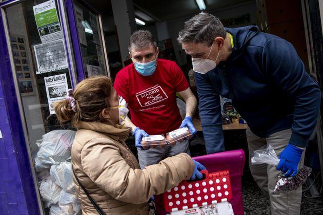 Una mujer recibe alimentos de una asociación de vecinos del barrio de