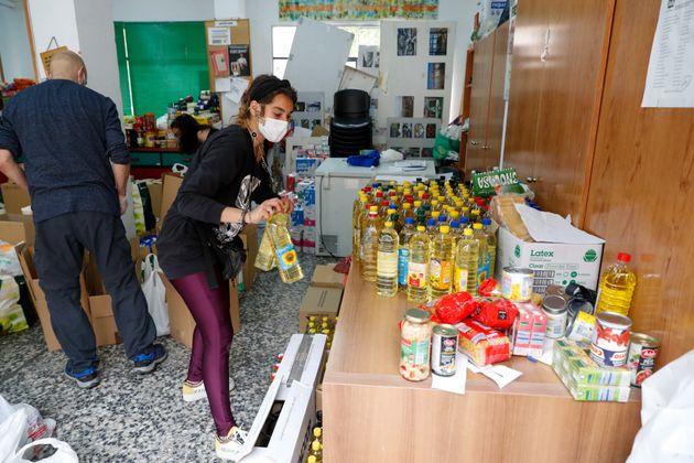 Un grupo de voluntarios organiza la comida del banco de alimentos de la asociación de vecinos durante...