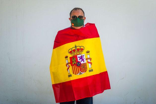 Un hombre envuelto en una bandera de española y con una máscara con la enseña