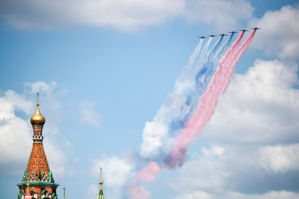 Russian warplanes fly over Red Square leaving trails of smoke in colors of national flag during the Victory...