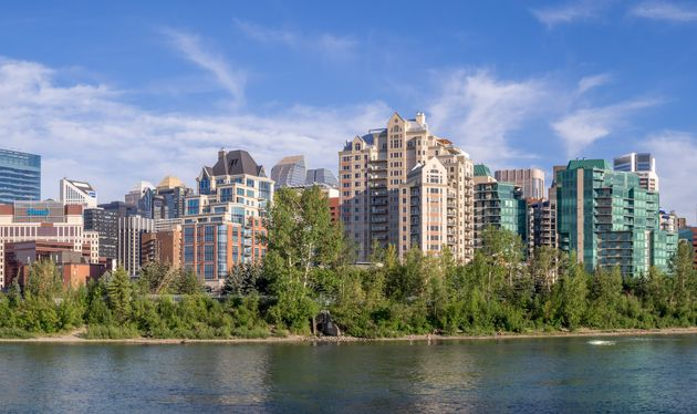 Condo towers line the Bow River in Calgary. CMHC says the city will take longer than others for its housing...
