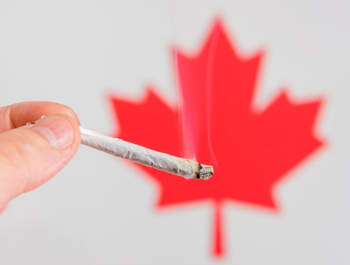 A hand holding a marijuana cigarette in front of a red maple leaf. The joint is lit and smoke rises from it. There is room for test above the joint.