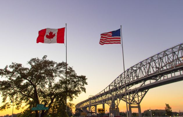 The Canadian and U.S. flags fly over the twin spans of the Blue Water Bridge between Sarnia, Ont., and...