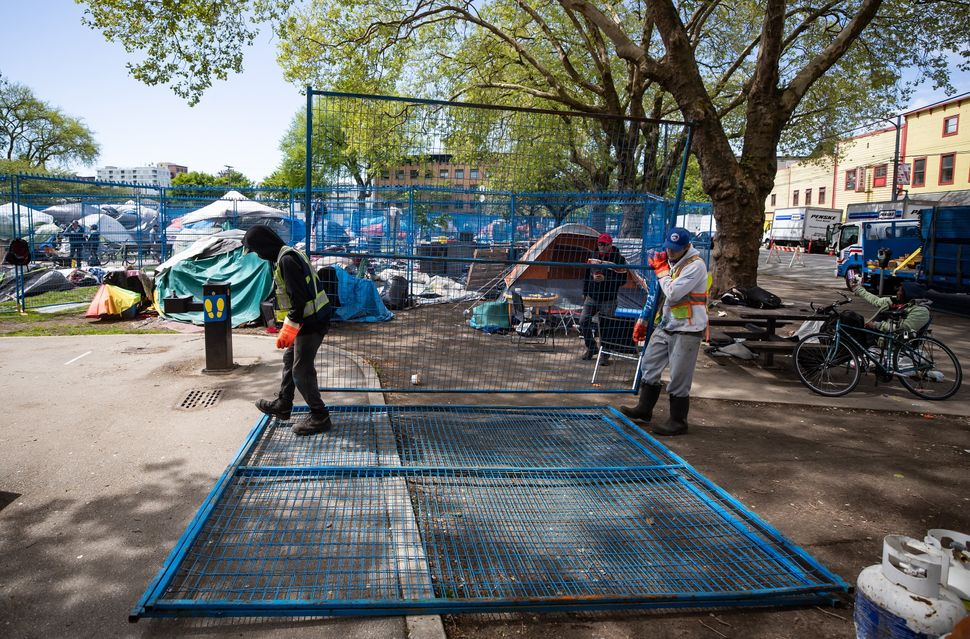 Workers deliver fencing to a homeless camp at Oppenheimer Park in the Downtown Eastside of Vancouver,...
