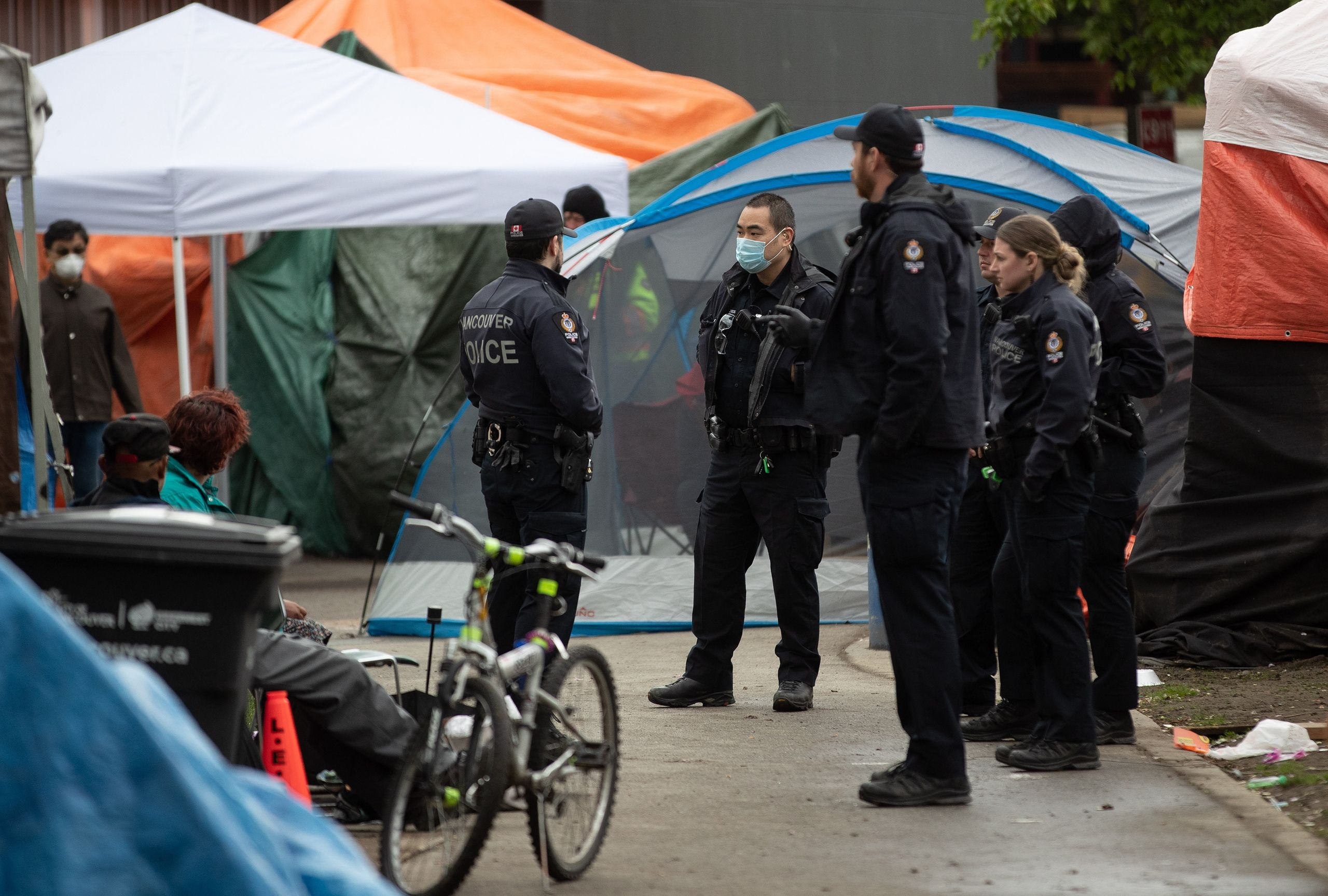 Police officers are seen at a homeless camp at Oppenheimer Park in the Downtown Eastside in Vancouver, on  April 26, 2020.