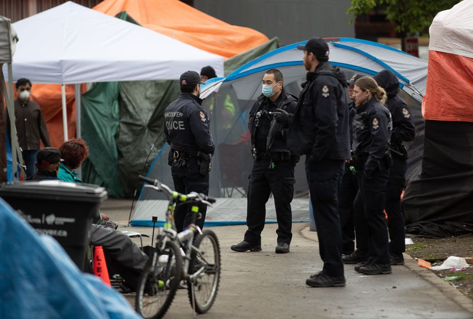 Police officers are seen at a homeless camp at Oppenheimer Park in the Downtown Eastside in Vancouver,...