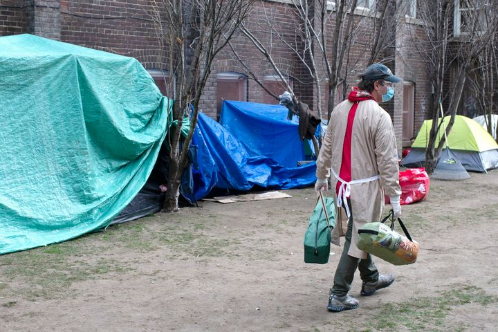 Doug Johnson Hatlem, a worker at The Sanctuary, a respite centre in Toronto, carries tents to be distributed to members of the homeless community on April 19 2020.
