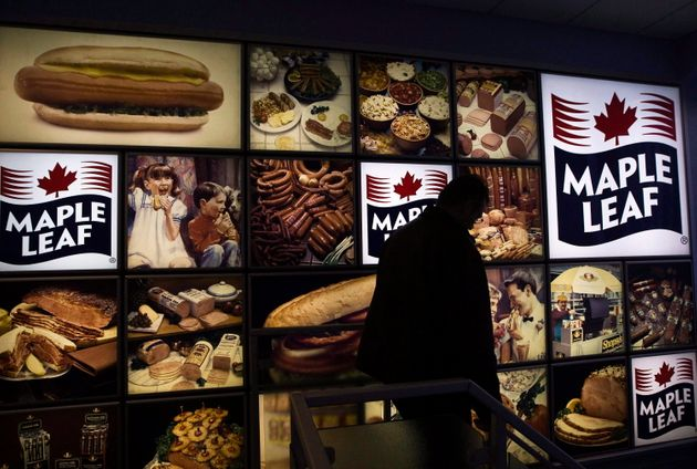 A Maple Leaf Foods employee walks past a Maple Leaf sign at the company's meat facility in Toronto on...