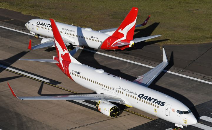 Qantas 737-800 aircraft parked on the east-west runway at Sydney Airport.