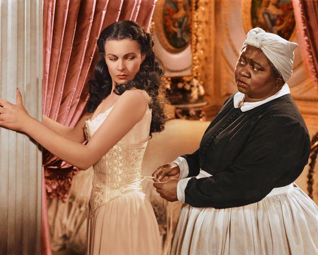 『風と共に去りぬ』の一場面。主人公のコルセットを閉める、俳優のハティ・マクダニエル氏(右)