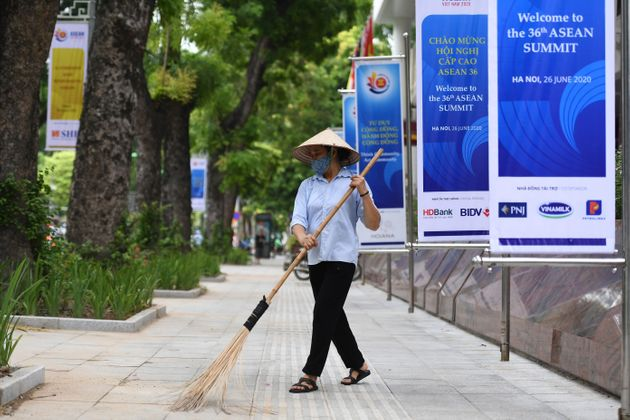 A woman sweeps the street next to banners for the 36th ASEAN Summit by the International Convention Cente in Hanoi on June 25, 2020, a day before the summit is set to be held online due to the COVID-19 coronavirus pandemic. (Photo by Nhac NGUYEN / AFP) (Photo by NHAC NGUYEN/AFP via Getty Images)