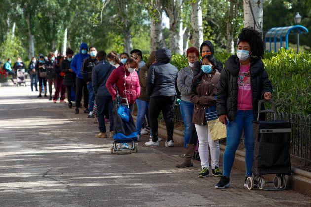 Una cola de ciudadanos esperando para recoger comida en