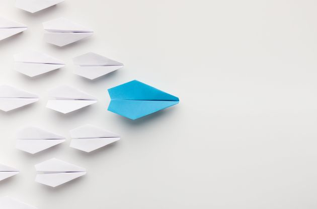 Religious leader. One blue paper plane leading group of white ones, top view, copy space