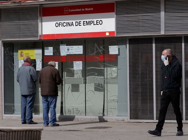 Dos personas frente a la puerta una oficina del paro en