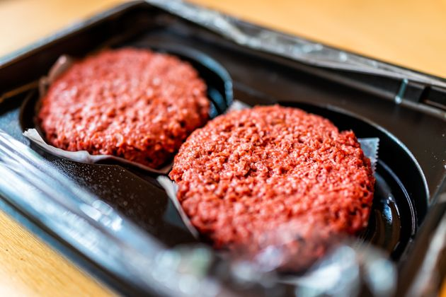 Closeup of two raw uncooked red vegan meat burger patties in plastic
