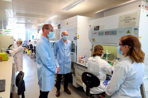 William, wearing a face mask, meets scientists including Christina Dold (R) during a visit to the manufacturing...